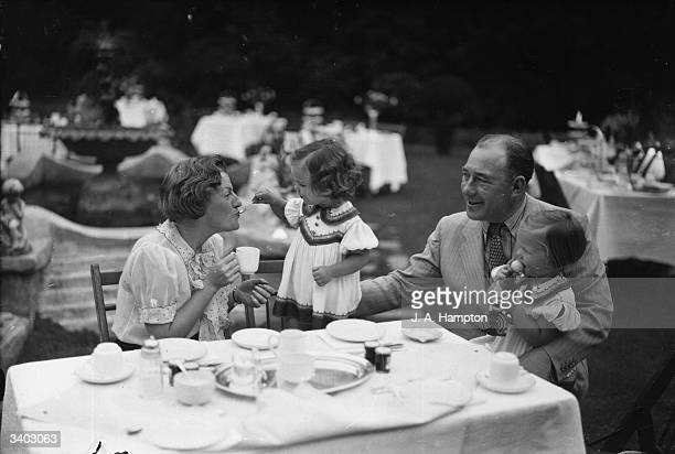 English music hall star Gracie Fields being fed by one of the twin daughters of film comedian Leslie Fuller The twins are celebrating their second...