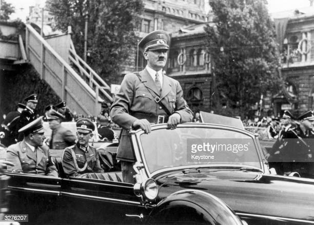 The Chancellor of Germany Adolf Hitler standing in his car as he travels through the ancient town of Nuremberg to open the Nazi Congress In the rear...