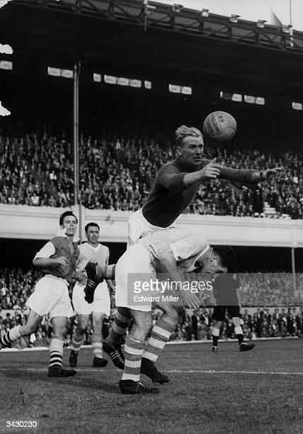 Manchester City's goalkeeper Bert Trautmann making a save during a game against Arsenal at Highbury London