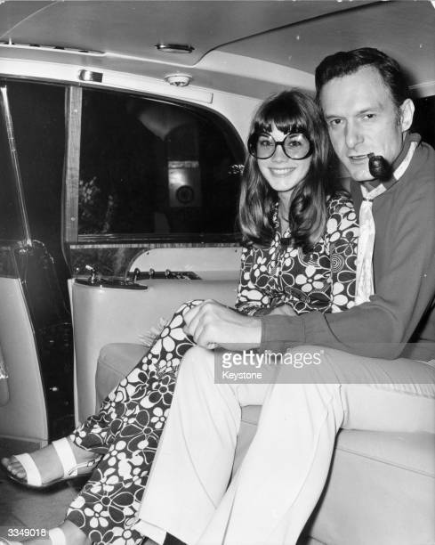 American pornograpic magazine publisher and club owner Hugh Hefner with American actress Barbara Benton in a car leaving London's Hilton Hotel for...