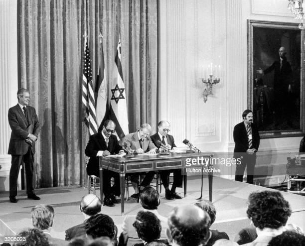 Egyptian President Anwar Sadat President Jimmy Carter and Israeli Prime Minister Menachem Begin sign tentative agreements for peace in the Middle...