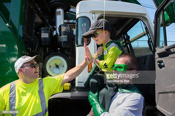 6yearold Ethan Dean who was diagnosed with cystic fibrosis at two weeks old gets a high five while carried by Capt Recycle Mitch Zak during his stop...