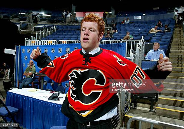 70th overall pick John Negrin of the Calgary Flames puts on his new team jersey after being drafted in the 2007 NHL Entry Draft at Nationwide Arena...