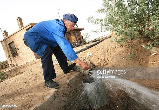 70year old farmer Qi Shenglian gets water from a deep well dug in the ground of what used to be the Tengeli desert on May 8 2007 in Ningxia Province...