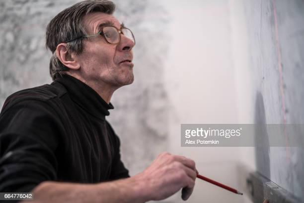70-jaar-oud actieve senior man, bouwvakker - loodgieter, doen measurments