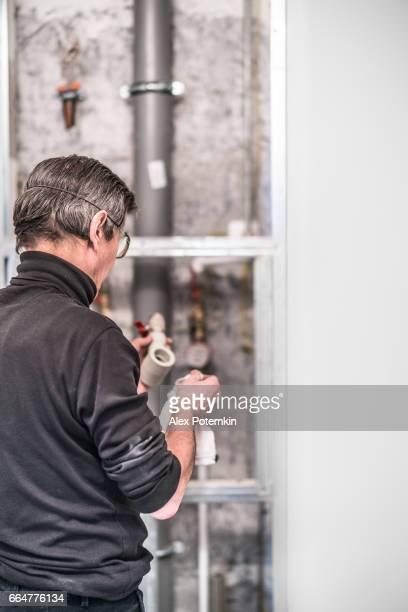 70-jaar-oud actieve senior man, bouwvakker - loodgieter, die werkt voor home renovatie