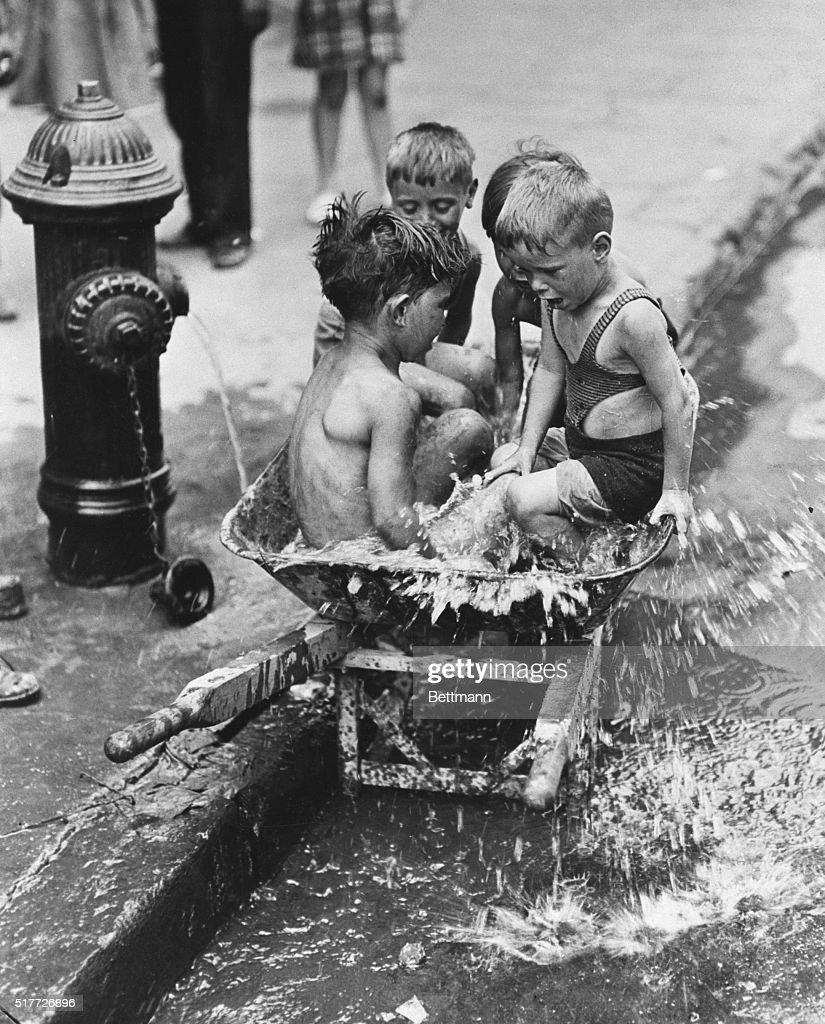 Boys Splashing by a Fire Hydrant : News Photo