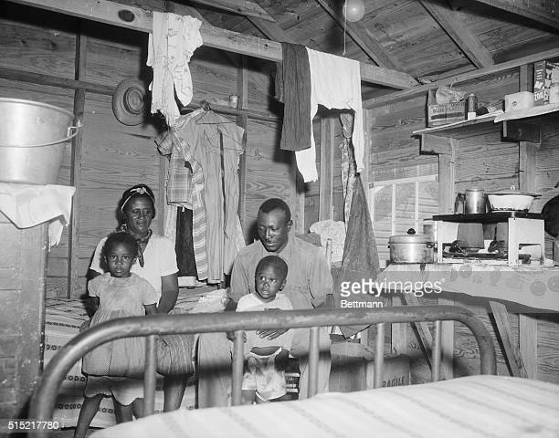 7/11/1958Cheriton Virginia Six adult migrant farm workers including this family of four are housed in this 10x14 foot one room wooden shack in a...