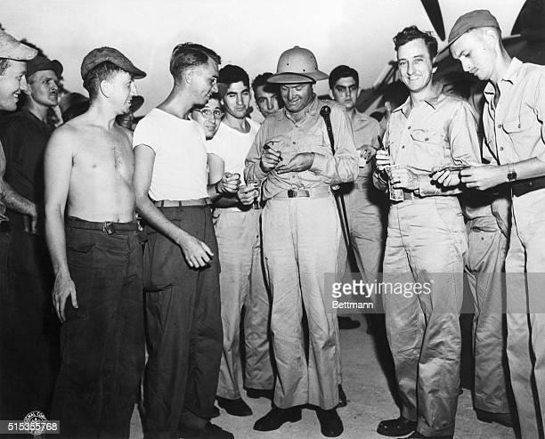 Espiritu Santo, New Hebrides- Bob Hope signs autographs for some of the 1000 servicemen who met his plane at the Pekoa Airfield.