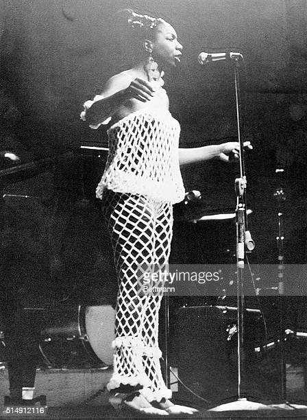 Newport, RI- Nina Simone wears a revealing net costume at Newport Jazz Festival. She is shown singing on stage.