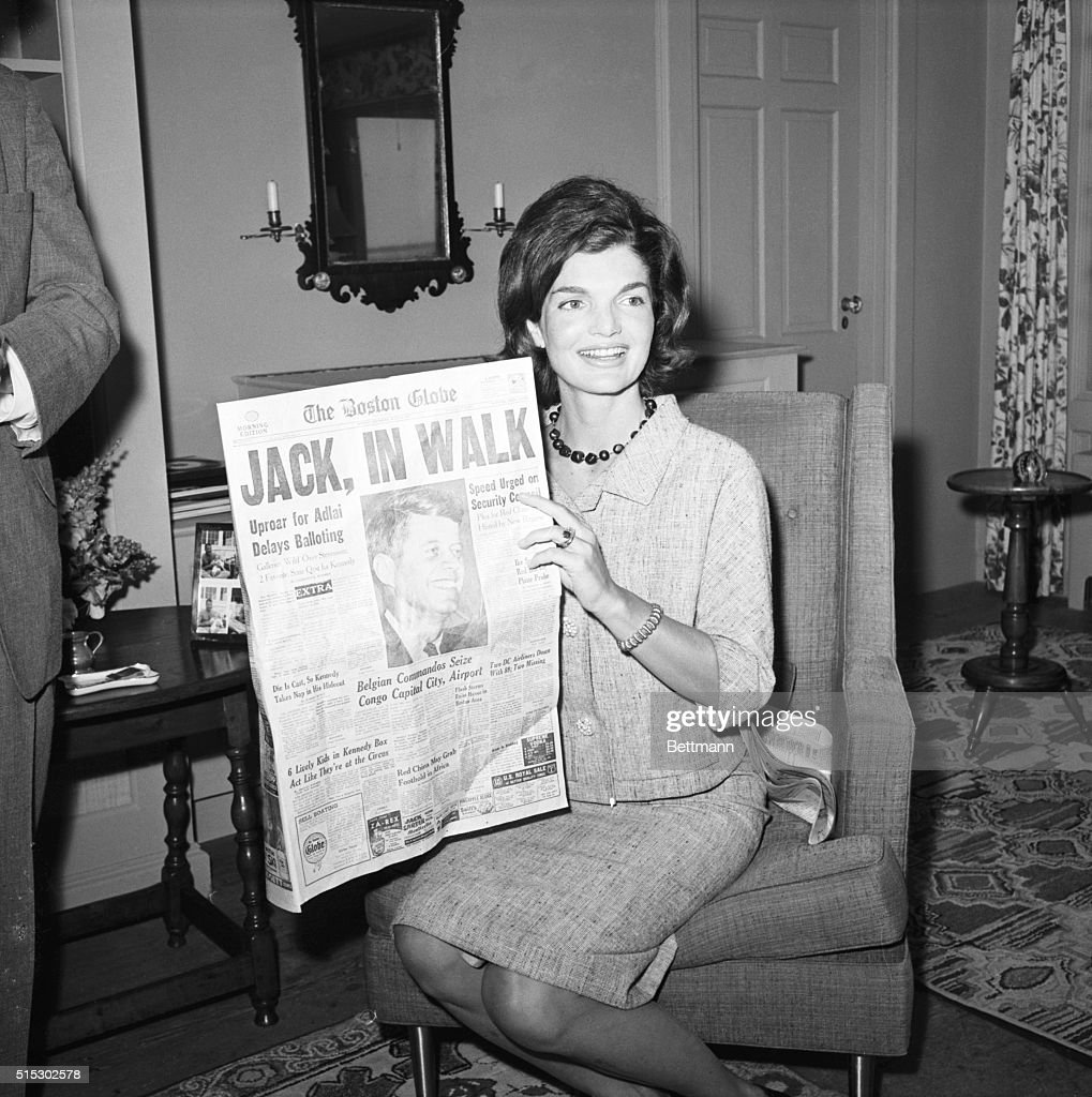 Hyannis Port, MA- Mrs. John F. Kennedy beams as she reads the paper telling of her husband, Senator John F. Kennedy's first ballot victory for the presidential nomination of the Democratic party. She is shown here meeting the press.