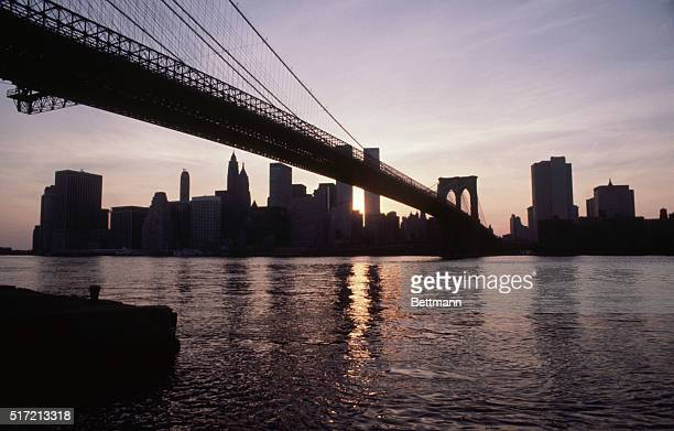 View of New York City skyline and Brooklyn Bridge during blackout with no lights remaining on Buildings are silhouetted by sunset