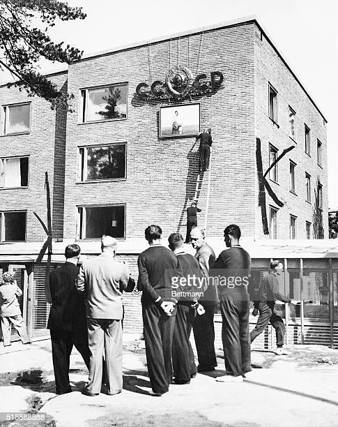 7/16/1952Helsinki Finland Members of the Russian Olympic team are shown putting a portrait of Marshal Stalin beneath the hammer and sickle motif on...