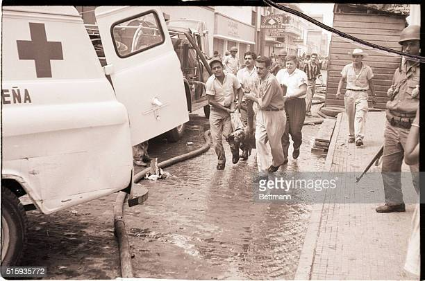 Tegucigalpa, Honduras-An injured man is carried to a waiting ambulance as government troops move to crush the bloody revolt attempt which erupted...