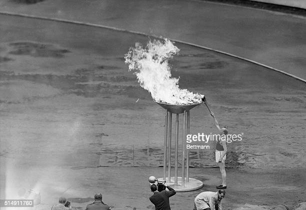 Helsinki, Finland- Finland's Paavo Nurmi lights the 1952 Olympic fire with the tourch he carried into the Helsinki Stadium, July 19, to officially...