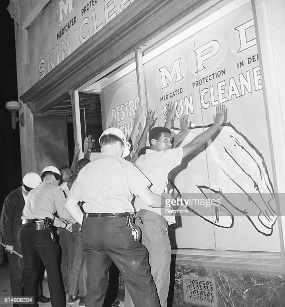 Cleveland, OH- Police search Negro youths after a fire bomb was thrown at a building. They were released and told to go home. Cleveland's east side...