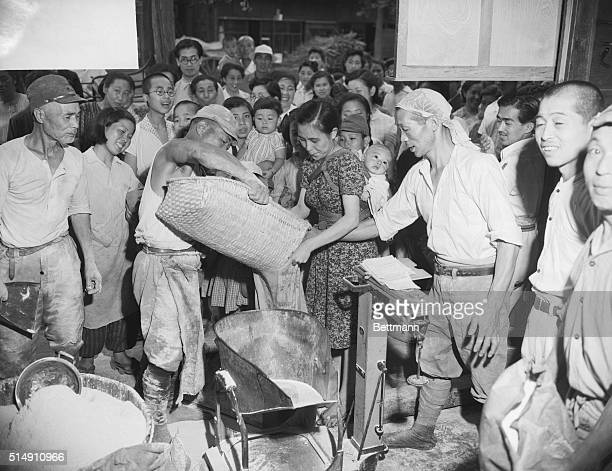 7/2/1946Tokyo JapanA workman is shown handing out individual rations of the largest single amount of US food ever released in Japan250 tons of wheat...