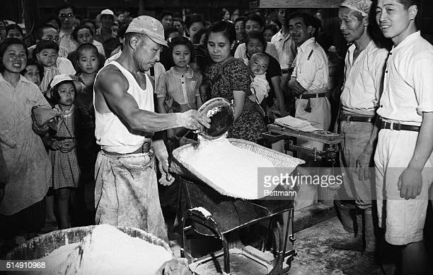 7/2/1946Tokyo JapanA workman is shown measuring the amount of food handed out in individual rations of the largest single amount of US food ever...