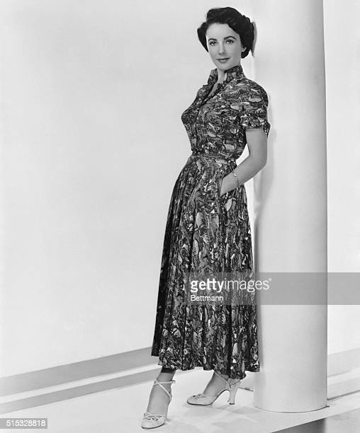 7/2/1949Hollywood CA Vivid green coral blue and yellow are combined in the tropical print frock by Ceil Chapman designed for actress Elizabeth...