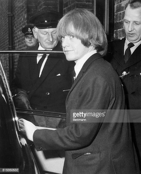 7/22/1965London England Longhaired Brian Jones wearing a bright green jacket grins as he steps into a waiting car outside a London Magistrate's court...