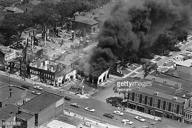 The gutted remins of buildings attest to the destruction caused by two days of rioting in Detroit's west side A service station continues to burn...