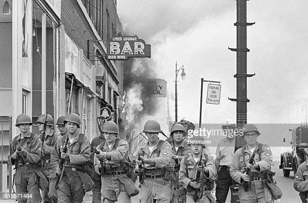 Toughlooking Michigan National Guardsmen push rioting Negroes back from a burning building with fixed bayonets on Detroit's riottorn west side...