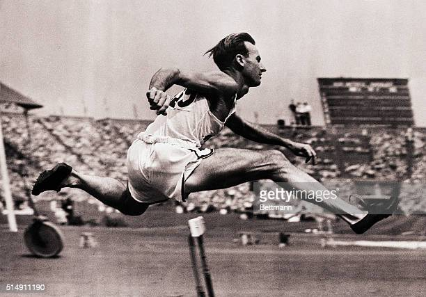 Wembley, England- Roy Cochran goes over a hurdle in trial heat on July 29. Cochran went on to cop the 400-meter hurdle event at the Olympics in new...