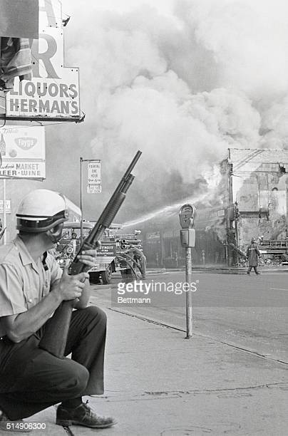 A policeman keeps his eyes on buildings in the area against possible sniper attack on firemen as they battle blaze during racial violence here 7/24...