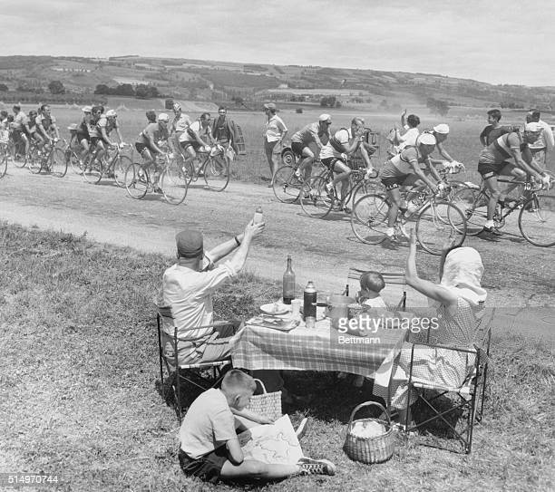 7/31/1954St Veraud France A picnicking French family gets almost no response to its cheery greeting to cyclists in the Tour De France bike race The...
