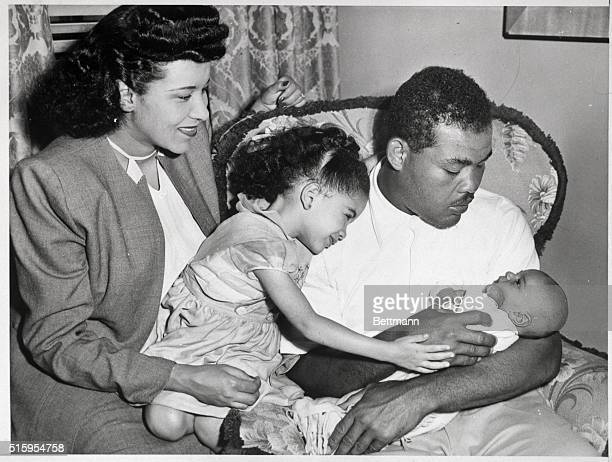 Chicago, IL- Boxing champion Joe Louis meets Joe, Jr. For the first time after Mrs. Marva Louis, their daughter Jackie, and the baby arrived by plane...