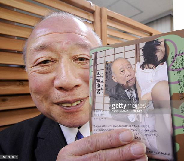 A 74yearold porno video actor Shigeo Tokuda smiles as he shows an advertisement poster of his video at a Tokyo video shop on March 5 2009 Tokuda...