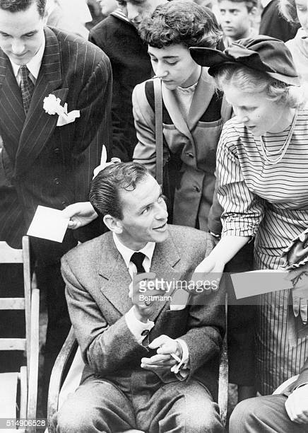 7/7/1950London England Singer Frankie Sinatra gives his autograph to girl fans at the Independence Day reception given by Lewis Douglas US Ambassador...