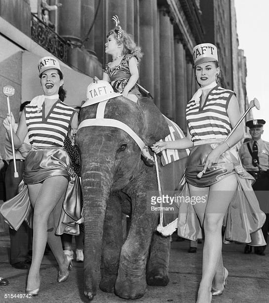 7//7/1952Chicago Illinois Two curvaceous gals and one little gal not quite eligible for curves as yet lead the GOP elephant down Chicago's Michigan...