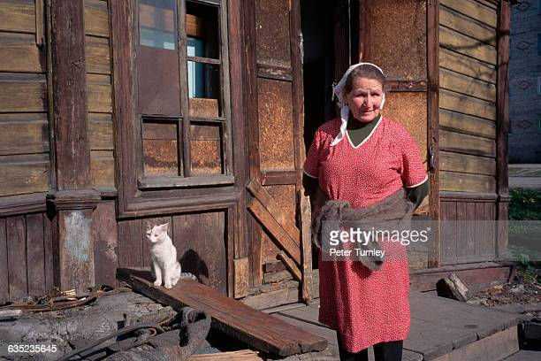 77yearold Agnay Ivanova stands outside her door with one of her cats She lives alone in a poor Siberian town suffering widespread economic problems...