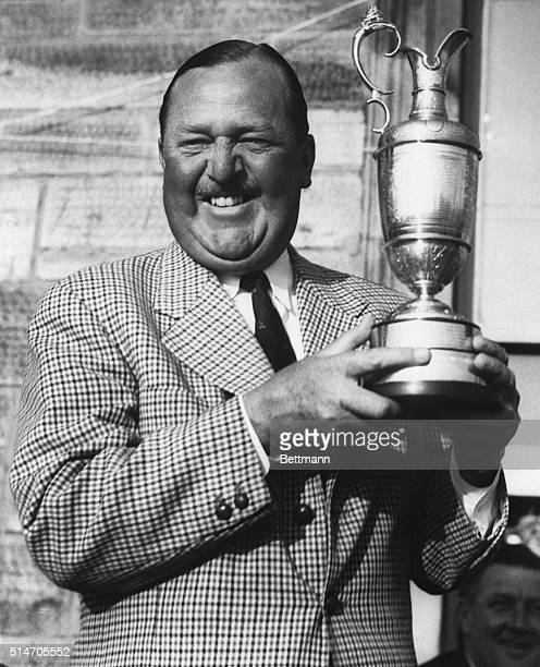 """Saint Andrews, Scotland: Arthur """"Bobby"""" Locke, of South Africa, flashes a toothy smile as he proudly holds up the cup he has won for the fourth time...."""