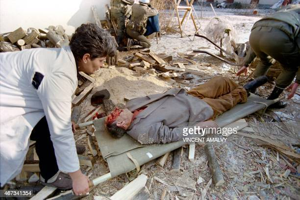 A 78yearold Bosnian carried on a stretcher is taken to cover after he was severely wounded in the head by a sniper while cutting some wood outside...