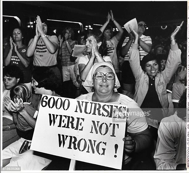 St. Paul, Minnesota- Striking registered nurse Lorrayne Lenarz, of Minneapolis, holds a sign while other nurses cheer at a union meeting shortly...