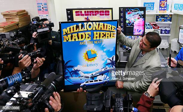 Eleven franchise owner Balbir Atwal right who will receive $1 million for selling a winning ticket holds a Powerball poster as media crowds around at...
