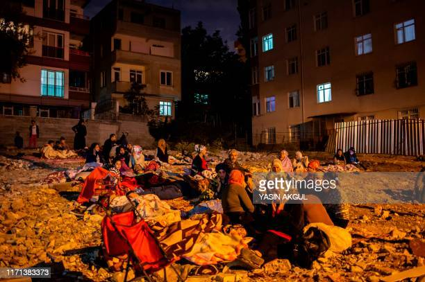 People sit on blankets in an empty lot after a 57 magnitude earthquake hit the Kucukcekmece district of Istanbul on September 27 2019 A 57magnitude...