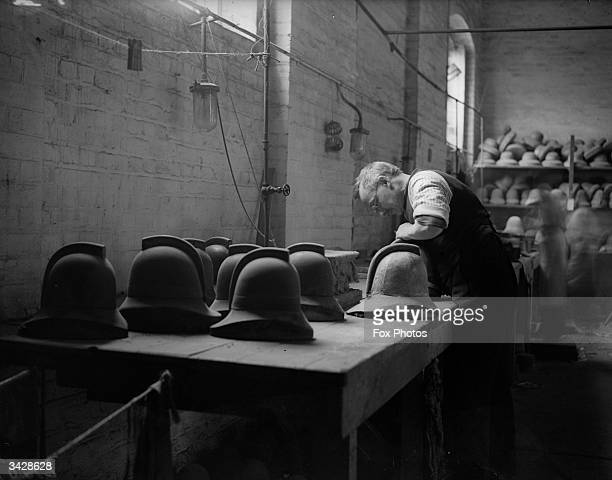 A workman produces a batch of policemen's helmets at a workshop in Tooley Street London