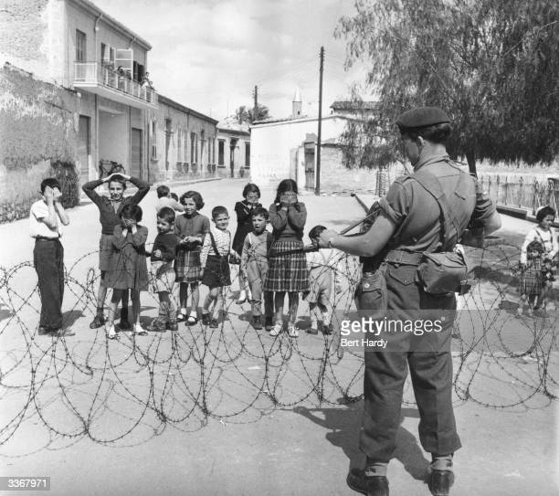 The net closes on EOKA terrorists in the mountainous districts of Cyprus as a British Marine guards the road and bewildered children look on The move...