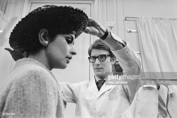 Yves SaintLaurent exwonder boy of Dior working with a fashion model at his own fashion house in Paris