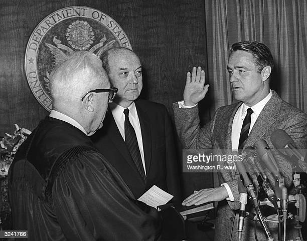US Chief Justice Earl Warren administers the oath of office to Sargent Shriver the new US Ambassador to France while Secretary of State Dean Rusk...