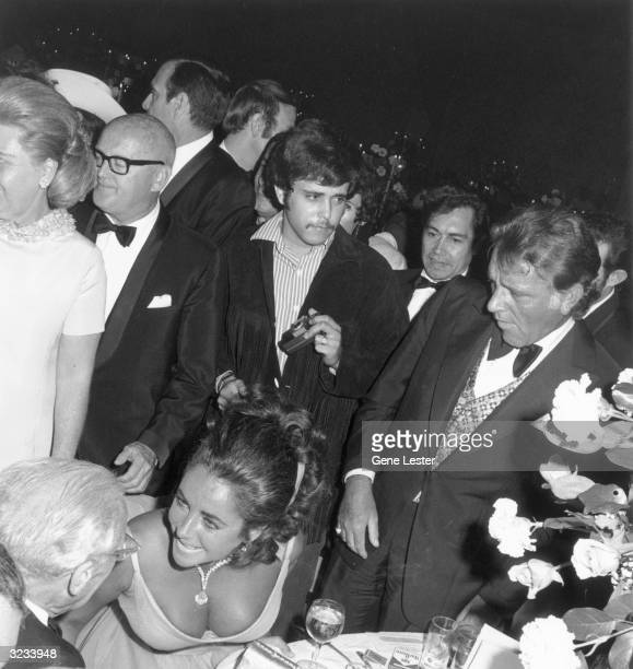 British-born actor Elizabeth Taylor leans forward to speak with an elderly man sitting at a table as her fifth husband, Welsh actor Richard Burton...