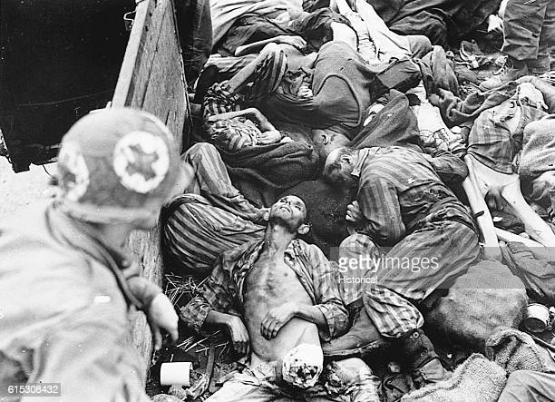 A US 7th Army medical corpsman newly arrived with liberating troops looks into a train car piled with the emaciated and mutilated corpses of men from...