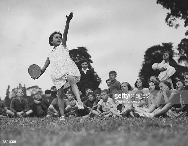 A girl throwing a tin lid as a makeshift discus at a gathering in Regent's Park inspired by the current Empire Games Other events involved broom...