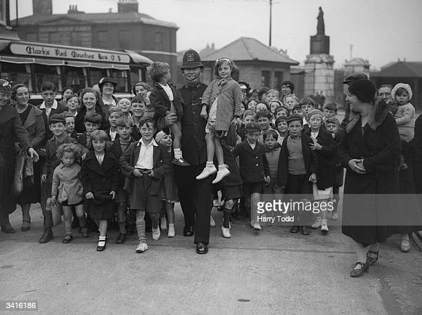 A group of children with a policeman at West India Docks London before setting off on a day's outing paid for by the Port of London Authority...
