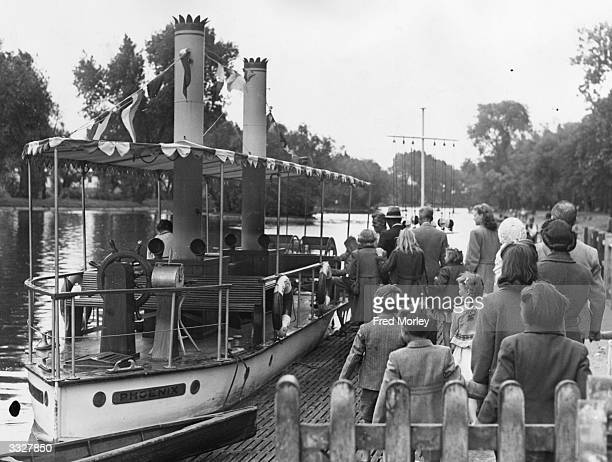Children queue up for a ride on the 'Phoenix' a miniature paddlesteamer in Barking Park Essex The small craft is made out of a converted assaultcraft...