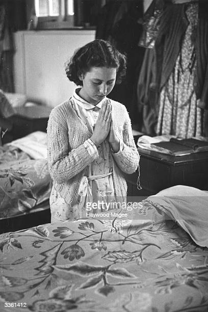 A girl kneeling by her bed saying good night prayers in the dormitory of Wakefield local authority's holiday school at Horsea on Sea Original...