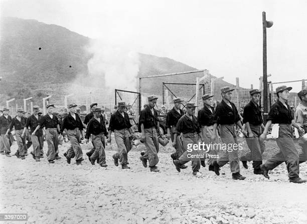 North Korean prisoners of war leaving a prison camp on Koja island to be transported to Inchon under a recent armistice.